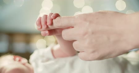 mateřský : 4k ,Parent holding newborns hand in Slow Motion . Happy Family Mother and her Newborn Baby together. Maternity concept. Parenthood. Motherhood. Magic light bokeh background Dostupné videozáznamy