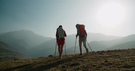 turk : Hiking couple walking on trail. Healthy lifestyle hiker people walking in mountains. Young woman and man travel to honeymoon, steadycam shot