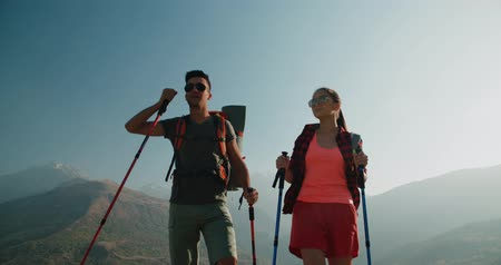 sağlıklı yaşam : Hikers people hiking - healthy active lifestyle. Hiker people hiking in beautiful mountain nature landscape. Woman and man hikers walking during trekking hike.steadycam shot Stok Video