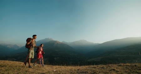 multikulturní : young active Asian couple travelling in the mountains during their honeymoon, Steadicam shot