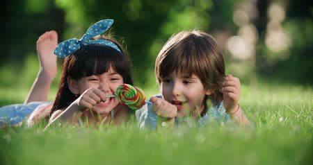 леденец : two small children,Caucasian boy and Asian girl having fun in the Park with a Lollipop Стоковые видеозаписи