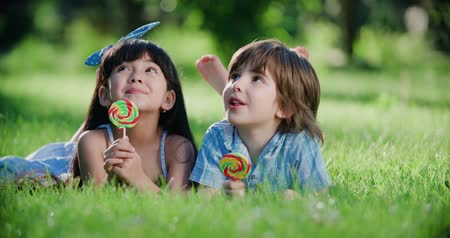 lollipop : two small children,Caucasian boy and Asian girl having fun in the Park with a Lollipop Stock Footage