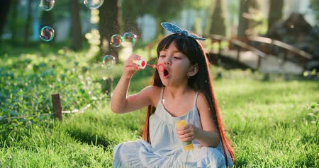 pigtail : close-up of Happy little Asian girl blowing soap bubbles in spring Park. Slow motion Stock Footage