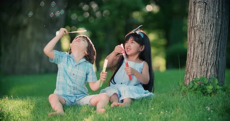 hůlky : Happy child blowing soap bubbles in spring park. Slow motion