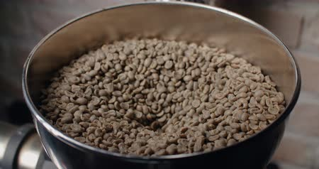 grãos de café : high quality raw Arabica coffee beans sprinkle in roaster machine