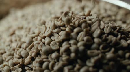 coffee grounds : slow motion raw Arabica coffee beans falling into the roaster machine