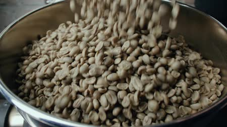 dark green : slow motion raw Arabica coffee beans falling into the roaster machine