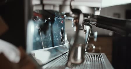 bung : Barista at work in the cafe, close-up. Coffee making process in professional coffee machine.
