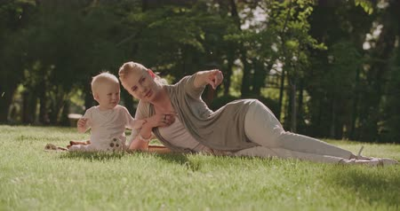happy emotional family moments, young mom with baby, fun playing on the grass on a Sunny summer day in the Park, slow motion Wideo
