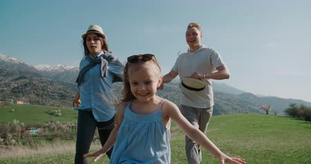 family idyll concept, a young family with a little daughter run happily, have fun in a beautiful mountain place, slow motion
