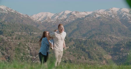 family idyll concept, a young happy family with a little daughter, have fun in a beautiful mountain place, slow motion Стоковые видеозаписи