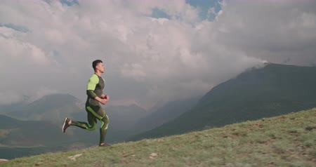 young confident man jogging in mountains in morning 4k