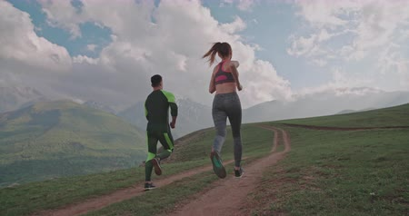 genç çift : active healthy couple running in mountains in morning 4k