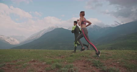 casal heterossexual : caicasian couple training and jogging in mountains in morning 4k