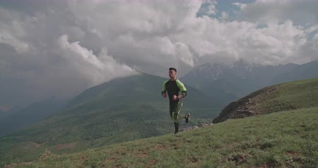 young handsome man running in mountains in morning 4k