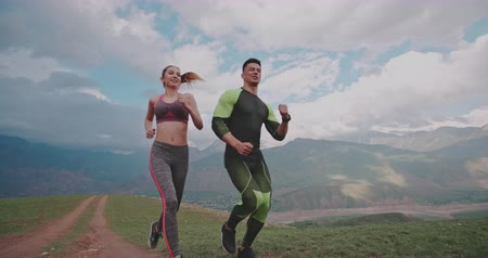 encouraging : young active couple exercising in mountains in morning 4k