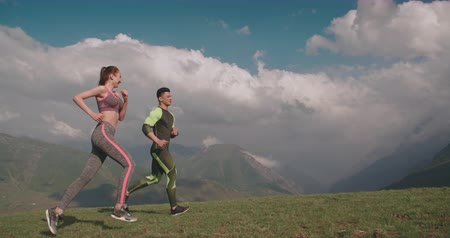 active healthy couple running in mountains in morning 4k