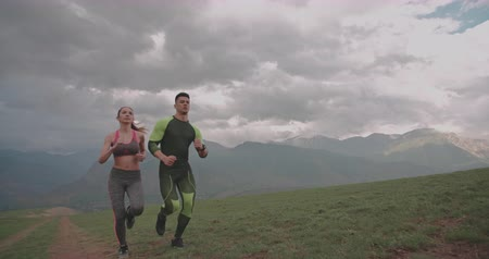 young active couple exercising in mountains in morning 4k