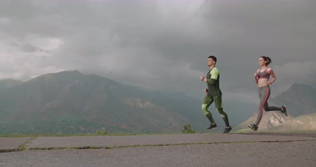 caicasian couple training and jogging in mountains in morning 4k