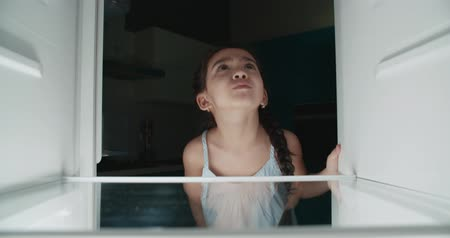 sad asian little girl looking in empty refrigerator, looking for products and does not find anything