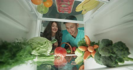 életmód : young cute asian couple putting healthy vegetables from basket to fridge and smiling - healthy way of life, wealthiness concept 4k