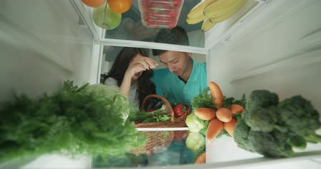canto : young cute asian couple putting healthy vegetables from basket to fridge and smiling - healthy way of life, wealthiness concept 4k