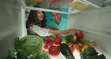 young cute asian couple putting healthy vegetables from basket to fridge and smiling - healthy way of life, wealthiness concept 4k