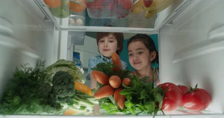 canto : little turkish brother and sister searching in fridge and choosing from vegetables 4k