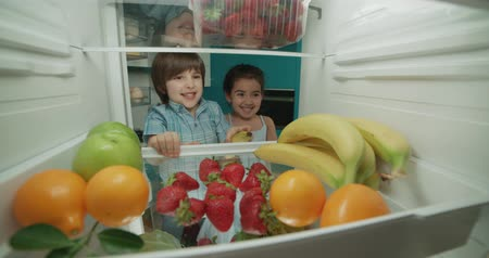 ataque : little cute turkish brother and sister searching in fridge and choosing from tasty fruits 4k Vídeos
