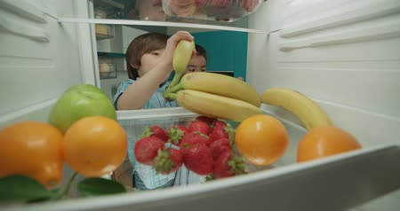 little indian brother and sister looking in fridge choosing fruits 4k Wideo