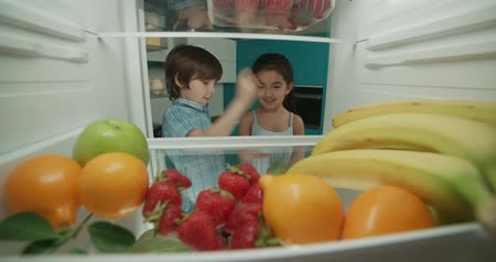 сестры : little indian brother and sister looking in fridge choosing fruits 4k Стоковые видеозаписи