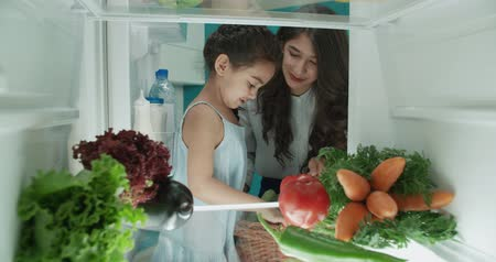 young cute asian family of three choosing vegetables from the fridge - family, wealthiness, healthy way of life concept 4k Wideo