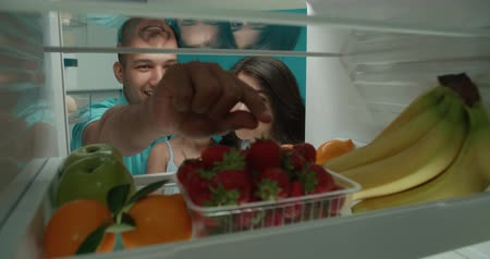 happy young family looking in fridge searching for fruits they need 4k - family, healthy way of life concept Стоковые видеозаписи