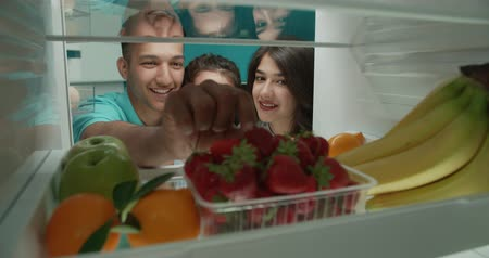 happy young family looking in fridge searching for fruits they need 4k - family, healthy way of life concept Wideo
