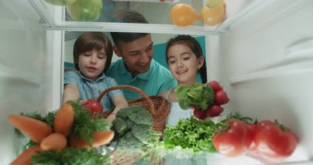 young cute asian family of three choosing vegetables from the fridge - family, wealthiness, healthy way of life concept 4k Стоковые видеозаписи