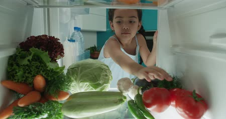little cute asian girl searching in fridge choosing healthy vegetables 4k
