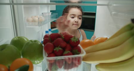 Little cute asian girl trying to reach out and pick fruits from fridge 4k