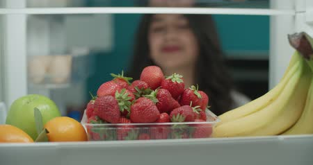 young attractive asian woman searching in fridge for fruits 4k - diet, healthy way of life concept Wideo