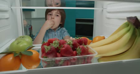 little cute turkish boy searching in fridge for tasty fruits 4k Wideo