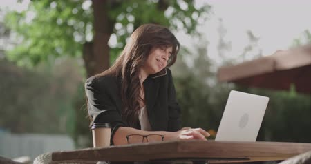 young female freelancer working in cafe outdoors 4k