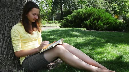 İncil : Teen girl reads the Bible sitting in the park