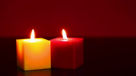 boŻe narodzenie : Two burning candles against red background