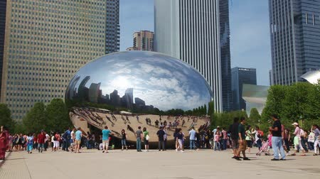 площадь : Cloud Gate sculpture in Millenium park with tourists on May 18, 2013 in Chicago, IL. Its a public sculpture by Indian-born British artist Anish Kapoor, is the centerpiece of the AT&T Plaza in Millennium Park within the Loop community area of Chicago, Ill Стоковые видеозаписи