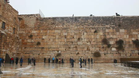 pielgrzymka : JERUSALEM - DECEMBER 12: The Western Wall with praying pilgrims on December 12, 2013 in Jerusalem. Its located in the Old City of Jerusalem at the foot of the western side of the Temple Mount.