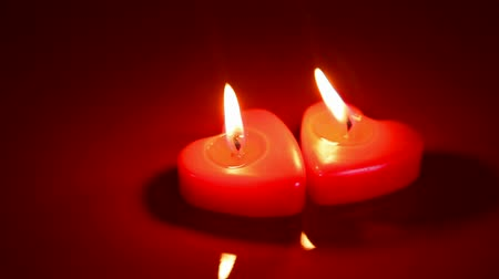 Two heart shaped burning candles against red background