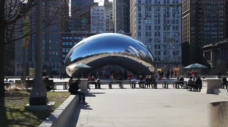 CHICAGO - APRIL 9: Cloud Gate sculpture with tourists in Millenium park on April 9, 2014 in Chicago, IL. This public sculpture is the centerpiece of the AT&T Plaza in Millennium Park within the Loop community area. Stock Footage