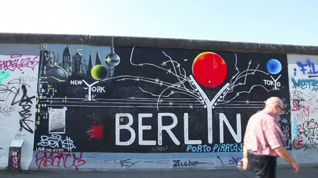 BERLIN - OCTOBER 3, 2014: The Berlin wall with grafitti on October 3, 2014 in Berlin, Germany. It was a barrier that existed from 1961 through 1989 to completely cut off West Berlin from surrounding East Germany. Stock Footage