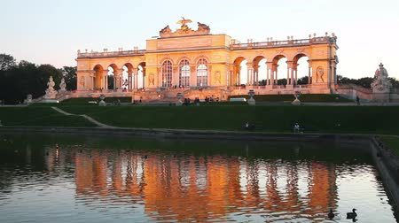VIENNA - OCTOBER 19: Gloriette Schonbrunn at sunset with tourists on October 19, 2014 in Vienna. Its the largest gloriette in Vienna built in 1775 as the last building constructed in the Schonbrunn garden.