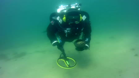 antika : Diver with a metal detector found a pot with antique coins, Baikal, Siberia, Eurasia
