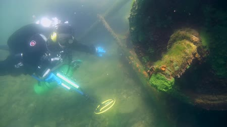 atrás : Diver with the metal detector searching for underwater treasure near to the wrack railway carriage, Baikal, Siberia, Eurasia Stock Footage